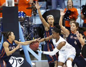 Photo - North Carolina's Diamond DeSheilds looks to make a pass under pressure from UT Martin players Heather Butler, left, Ashia Jones, and Elizabeth Masengil (4) during the first half of a first-round game in the NCAA women's college basketball tournament, Sunday, March 23, 2014, in Chapel Hill, N.C. (AP Photo/Ellen Ozier)