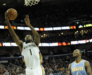 Photo - New Orleans Pelicans guard Tyreke Evans (1) scores two of his game high 19 points in front of Denver Nuggets guard Jordan Hamilton (1) in the second half of an NBA basketball game in New Orleans, Friday, Dec. 27, 2013. New Orleans won 105-89. (AP Photo/Stacy Revere)