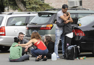 Photo - Hofstra University students gather near the house where another student and an armed intruder were killed during an overnight house break-in next to the campus, Friday, May 17, 2013, in Uniondale, N.Y. (AP Photo/ Louis Lanzano)
