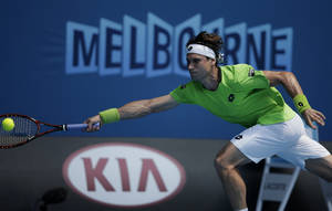 Photo - David Ferrer of Spain makes a forehand return to Adrian Mannarino of France during their second round match at the Australian Open tennis championship in Melbourne, Australia, Wednesday, Jan. 15, 2014.(AP Photo/Rick Rycroft)