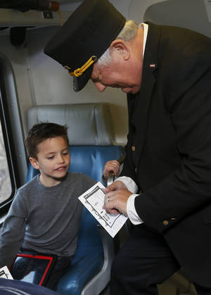 Photo - Conductor Neil Bagaus of Orlando, Fla., punches the train ticket of Lex McNeil of Jenks, Okla., on a demonstration ride of the Eastern Flyer passenger train from Sapulpa to the Oklahoma City metro area, Sunday, Feb. 23, 2014. Photo by Nate Billings, The Oklahoman