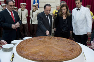 "Photo - In this photo dated Tuesday Jan. 7, 2014, French President Francois Hollande, center, and his partner Valerie Trierweiler cut slices of a traditional epiphany cake at the Elysee palace, in Paris. The woman considered France's first lady was hospitalized after a report the president is having an affair with an actress, her office said Sunday Jan. 12, as a poll was released showing the French shrugging off any liaison as none of their business. Valerie Trierweiler was hospitalized Friday, Jan. 10, the day the magazine report and photo spread came out — for ""rest and a few tests,"" said her chief of staff, Patrice Biancone. (AP Photo/Alain Jocard, Pool)"