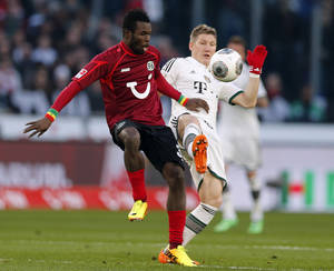 Photo - Bayern's Bastian Schweinsteiger, right, and Hannover's Mame Diouf of Senegal challenge for the ball during the German first division Bundesliga soccer match between Hannover 96 and Bayern Munich in Hannover, Germany, Sunday, Feb. 23, 2014. (AP Photo/Frank Augstein)