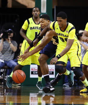 Photo - Baylor Royce O'Neale, right, battles Oral Roberts forward Denell Henderson (34), left, for a loose rebound in the first half of an NCAA college basketball game, Monday, Dec. 30, 2013, in Waco, Texas. (AP Photo/Waco Tribune Herald, Rod Aydelotte)