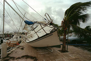 Photo - FILE - In this Aug. 24, 1992 file photo, a sailboat sits on a sidewalk at Dinner Key in Miami after it was washed ashore by Hurricane Andrew. Global warming is rapidly turning America into a stormy and dangerous place, with rising seas and disasters upending lives from flood-stricken Florida to the wildfire-ravaged West, the National Climate Assessment concluded Tuesday, May 6, 2014.  (AP Photo/Terry Renna, File)