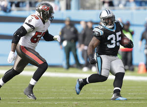 Photo - Carolina Panthers' Mike Tolbert (35) runs past Tampa Bay Buccaneers' Mason Foster (59) in the first half of an NFL football game in Charlotte, N.C., Sunday, Dec. 1, 2013. (AP Photo/Bob Leverone)