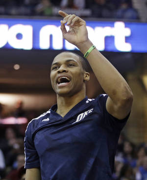 Photo - Oklahoma City Thunder's Russell Westbrook cheers on his team during the first quarter of an NBA basketball game against the Cleveland Cavaliers on Thursday, March 20, 2014, in Cleveland. Oklahoma City defeated Cleveland 102-95. (AP Photo/Tony Dejak)