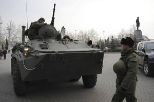 Photo - A Russian armored personnel carrier is driven on a street in Sevastopol, Ukraine's Black Sea Port that hosts a major Russian navy base Tuesday, Feb. 25, 2014. Tensions were building up in the Crimea, where ethnic Russians who make the majority of the local population are deeply suspicious of the new Ukrainian authorities who replaced fugitive Russia-backed President Viktor Yanukovych. (AP Photo/Andrew Lubimov)
