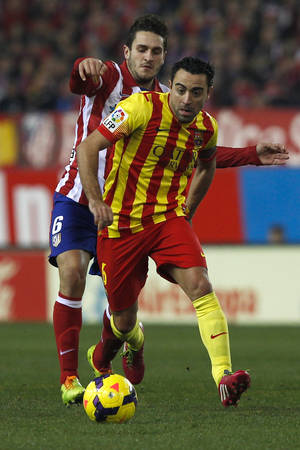 Photo - Barcelona's Xavi Hernandez in action with Atletico's Koke during a Spanish La Liga soccer match between Atletico de Madrid and FC Barcelona at the Vicente Calderon stadium in Madrid, Spain, Saturday, Jan. 11, 2014. (AP Photo/Gabriel Pecot)