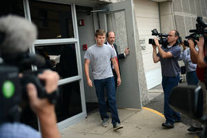 Photo - Spec Mellencamp, center, leaves the Monroe County Jail after being booked in to and bonded out of jail in Bloomington, Ind., Friday, Aug. 16, 2013. Speck Mellencamp and his brother Hud Mellencamp, 19, sons of rock star John Mellencamp, face felony battery charges stemming from a July incident during which police say they punched and kicked a 19-year-old man they assaulted on his front porch. Ty Smith, son of Indiana University baseball coach Tracy Smith, and an IU football team freshman walk-on, also faces felony battery charges from the same incident. (AP Photo/ by/The Herald-Times, Chris Howell)