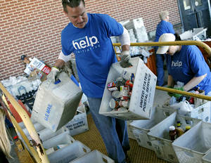 Photo - Doug Almgren, and other volunteers, sort through and load food into a truck during the Stamp Out Hunger food drive at the Britton Post Office in northwest Oklahoma City last May. Letter carriers collected nonperishable food donations from households on their route, according to the Regional Food Bank of Oklahoma. <strong>John Clanton - The Oklahoman, Archives</strong>