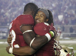 Photo - Florida State running back Devonta Freeman, right, hugs fellow unning back James Wilder Jr. after the team defeated Miami 41-14 in an NCAA college football game Saturday, Nov. 2, 2013, in Tallahassee, Fla. Freeman had three touchdowns in the win. (AP Photo/Steve Cannon)