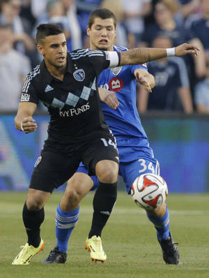 Photo - Sporting KC forward Dom Dwyer (14) works the ball forward while covered by Montreal Impact defender Karl Ouimette (34) during the first half of an MLS soccer match in Kansas City, Kan., Saturday, April 19, 2014. (AP Photo/Orlin Wagner)