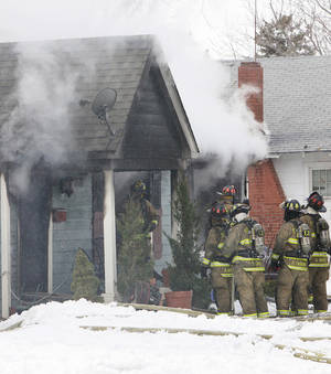 Photo - Firefighters try to save a house Friday at 3030 NW 15 in Oklahoma City. Photo by David McDaniel, The Oklahoman