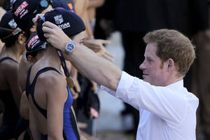 Photo - Britain's Prince Harry places a medal on a young swimmer after an exhibition swim during his visit to the Minas Tenis Club where England's Olympic team will practice during the 2016 Olympic and Paralympic Games in Belo Horizonte, Brazil, Tuesday, June 24, 2014. Prince Harry is in Brazil for the World Cup. (AP Photo/Bruno Magalhaes)