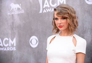 Photo - FILE - In this Sunday, April 6, 2014, file photo, Taylor Swift arrives at the 49th annual Academy of Country Music Awards at the MGM Grand Garden Arena in Las Vegas. Police in Rhode Island say they arrested three people outside Swift's beachfront home after they accosted security guards at the singer's property. Authorities say the three Connecticut residents were charged with misdemeanor breach of peace after they threw beer bottles and shouted expletives at the guards Sunday, June 15, 2014, outside Swift's house in the Watch Hill section of Westerly. Swift wasn't at the home at the time. (Photo by Al Powers/Powers Imagery/Invision/AP, File)