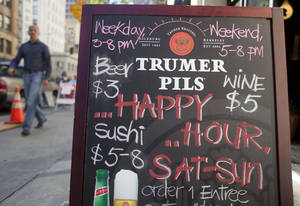 photo - In this photo taken Monday, Aug. 6, 2012, a  man walks past a sign advertising a happy hour at a restaurant on Second Street in San Francisco.  The concept of happy hour when bars offer lower prices or two-for-one specials seems like a widespread tradition, but is actually illegal or restricted in quite a few places. (AP Photo/Eric Risberg)