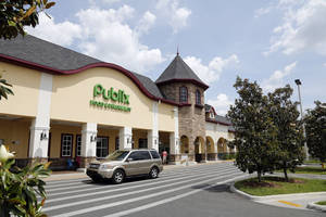 Photo - A vehicle passes the front of the Publix supermarket in Zephyrhills, Fla., Sunday, May 19, 2013. The highest Powerball jackpot worth an estimated $590.5 million was sold recently at this Publix supermarket. (AP Photo/Scott Iskowitz)