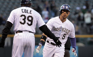 Photo - Colorado Rockies third base coach Stu Cole (39) congratulates Rockies' Carlos Gonzalez (5) after Gonzalez's home run in the first inning of a baseball game against the New York Mets in Denver, Thursday, May 1, 2014.(AP Photo/Joe Mahoney)
