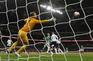 Photo - Germany's Per Mertesacker, center, scores pass England's goalkeeper Joe Hart, left, during the international friendly soccer match between England and Germany, at Wembley Stadium in London, Tuesday, Nov. 19, 2013. (AP Photo/Alastair Grant)