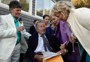 Photo - In this Sept. 21, 2013 photo, former President George H.W. Bush, seated center, prepares to sign the marriage license of longtime friends Helen Thorgalsen, right, and Bonnie Clement, left, in Kennebunkport, Maine, as officiant Nancy Sosa, third right, and Helen's daughter Lindsey, rear, look on. Bush was an official witness at the same-sex wedding, his spokesman said Wednesday, Sept. 25, 2013. (AP Photo/Susan Biddle)