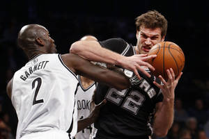 Photo - San Antonio Spurs' Tiago Splitter (22), of Brazil, is fouled by Brooklyn Nets' Kevin Garnett (2) during the first half of an NBA basketball game on Thursday, Feb. 6, 2014, in New York. (AP Photo/Jason DeCrow)