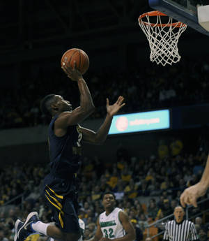 Photo - West Virginia's Juwan Staten (3) drives to the basket during the first half of an NCAA college basketball game against Marshall in Charleston, W.Va., on Saturday, Dec. 14, 2013. (AP Photo/Tyler Evert)