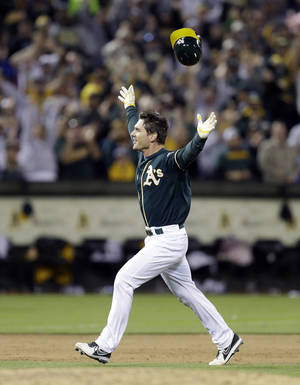 Photo - Oakland Athletics' John Jaso celebrates after making the game-winning hit against the Washington Nationals in the 10th inning of a baseball game Saturday, May 10, 2014, in Oakland, Calif. (AP Photo/Ben Margot)