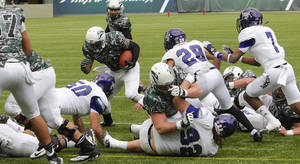 Photo - Weber State defenders hold Portland State's DJ Adams (10) away from the goal line during the first half of an NCAA college football game in Portland, Ore., Saturday Nov 2, 2013. (AP Photo/Greg Wahl-Stephens)