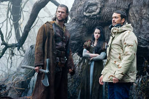 """Photo -   This film image released by Universal Pictures shows actors Chris Hemsworth, from left, Kristen Stewart and director Rupert Sanders on the set of """"Snow White and the Huntsman"""". Universal Pictures is continuing to pursue a sequel to """"Snow White and the Huntsman"""" in the wake of Kristen Stewart's affair with the film's director. Universal co-chairman Donna Langley said in a statement Wednesday that the studio is """"currently exploring all options to continue the franchise"""" and that reports of Stewart's exit """"are false."""" Since Stewart, who played Snow White in the film, and Rupert Sanders, the married, 41-year-old director of the film last month publically apologized for a tryst caught in photographs, the future of """"Snow White"""" has been uncertain. (AP Photo/Universal Pictures, Alex Bailey)"""