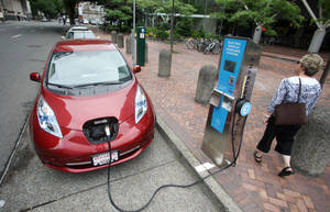 Photo - A Nissan Leaf charges at a electric vehicle charging station in Portland, Ore.  AP Photo