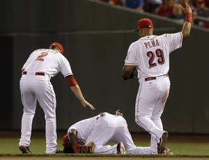Photo - Cincinnati Reds second baseman Brandon Phillips is checked by shortstop Zack Cozart (2) and first baseman Brayan Pena (29) after Phillips was injured in the eighth inning of a baseball game against the Chicago Cubs, Wednesday, July 9, 2014, in Cincinnati. Phillips was taken out of the game won by Cincinnati 4-1. (AP Photo/Al Behrman)