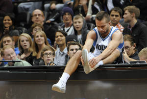 Photo -   Minnesota Timberwolves' Jose J.J. Barea ties his shoe after he wound up on the scorer and press table chasing a loose ball in the first half of an NBA basketball game against the Orlando Magic Wednesday, Nov. 7, 2012, in Minneapolis. The Timberwolves won 90-75. (AP Photo/Jim Mone)
