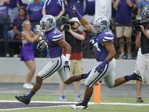 Photo - Kansas State defensive end Alauna Finau (94) celebrates as defensive back Kip Daily (7) runs an interception into the end zone during the first half of an NCAA college football game against Massachusetts in Manhattan, Kan., Saturday, Sept. 14, 2013. (AP Photo/Orlin Wagner)