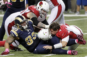 photo -   Arizona Cardinals quarterback Kevin Kolb, bottom right, is sacked by St. Louis Rams defensive tackle Jermelle Cudjo, bottom left, as Cardinals' Adam Snyder gets in on the play during the third quarter of an NFL football game, Thursday, Oct. 4, 2012, in St. Louis. Cudjo was charged with an unnecessary roughness penalty on the play. (AP Photo/Seth Perlman)