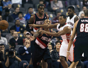 Photo - Toronto Raptors Kyle Lowry passes the ball past Portland Trail Blazers Damian Lillard during an NBA basketball game in Toronto on Sunday, Nov. 17, 2013. (AP Photo/The Canadian Press, Aaron Vincent Elkaim)