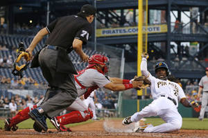 Photo - Cincinnati Reds catcher Brayan Pena, center, tags out Pittsburgh Pirates' Andrew McCutchen, right, in front of umpire Alan Haman to end the third inning of a baseball game in Pittsburgh Tuesday, June 17, 2014. McCutchen was attempting to score from third on a fly out to center field by Pirates Pedro Alvarez. (AP Photo/Gene J. Puskar)