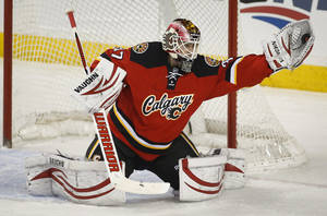 Photo - Calgary Flames goalie Joni Ortio, from Finland, makes a glove save during the first period of an NHL hockey game against the Ottawa Senators on Wednesday, March 5, 2014, in Calgary, Alberta. (AP Photo/The Canadian Press, Jeff McIntosh)