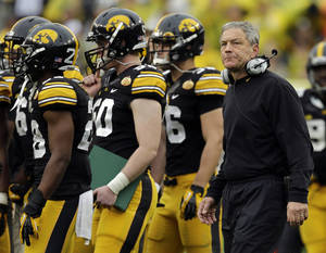 Photo - Iowa head coach Kirk Ferentz, right, walks with his team after they missed a field goal against LSU during the third quarter of the Outback Bowl NCAA college football game Wednesday, Jan. 1, 2014, in Tampa, Fla. (AP Photo/Chris O'Meara)