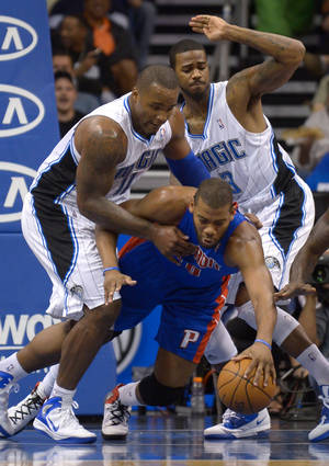 photo -   Detroit Pistons center Greg Monroe, center, dives for a loose ball between Orlando Magic center Glen Davis, left, and forward Earl Clark during the first half of an NBA basketball game in Orlando, Fla., Monday, April 9, 2012. (AP Photo/Phelan M. Ebenhack)