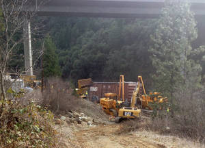 Photo - Crews work to remove one of four cars that derailed in Shasta County, Calif., on Tuesday, Jan. 28, 2014. Investigators say the train heading from Roseville, Calif., to Portland, Ore., derailed Monday. There were no injuries or hazardous materials spilled. (AP Photo/The Record Searchlight, Greg Barnette)