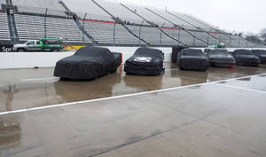 Photo - Trucks sit under covers as Air Titans try to keep the track dry during a rain delay at the  NASCAR Truck Series auto race at Martinsville Speedway in Martinsville, Va., Saturday, March 29, 2014. (AP Photo/Steve Sheppard)