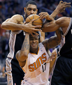 San Antonio Spurs' Tim Duncan pulls the ball away from Phoenix Suns' P.J. Tucker (17) during the second half of an NBA basketball game, Wednesday, Dec. 18, 2013, in Phoenix. The Spurs won 108-101. (AP Photo/Matt York)