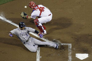 Photo -   Colorado Rockies' Carlos Gonzalez, left, scores past Philadelphia Phillies catcher Erik Kratz on a single by Wilin Rosario in the first inning of a baseball game, Friday, Sept. 7, 2012, in Philadelphia. Philadelphia won 3-2. (AP Photo/Matt Slocum)