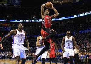 Photo - Toronto Raptors guard DeMar DeRozan, center, goes to the basket between Oklahoma City Thunder's Kendrick Perkins, left, and Serge Ibaka, right, during the first half of an NBA basketball game, Sunday, Dec. 22, 2013, in Oklahoma City. (AP Photo/Alonzo Adams)