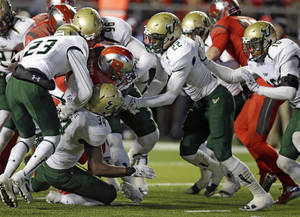 Photo - Rutgers running back Savon Huggins, center, pushes for yardage as he is surrounded by South Florida defenders during the second half of an NCAA college football game in Piscataway, N.J., Saturday, Dec. 7, 2013. Rutgers won 31-6.  (AP Photo/Mel Evans)