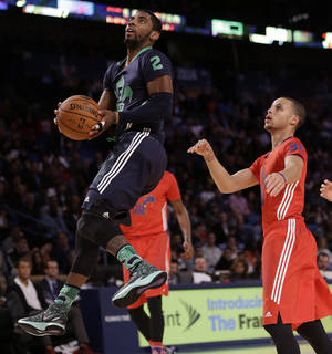 Photo - East Team's Kyrie Irving, of the Cleveland Cavaliers (2) goes to the hoop against the West Team during the NBA All Star basketball game, Sunday, Feb. 16, 2014, in New Orleans. (AP Photo/Gerald Herbert)