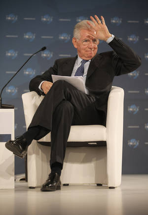 photo - Prime Minister of Italy Mario Monti gestures during the World Policy conference in Cannes, southern France, Saturday, Dec. 8, 2012.(AP Photo/Lionel Cironneau)