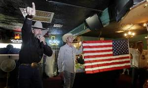 Photo - Auctioneer Hank Henke (left) from Bonham, TX takes bids on a new donated flag during the benefit  auction inside Marvin's Place Bar in Henryetta, OK June 6, 2010, to benefit the families of the slain  Weleetka, OK girls two years ago. MICHAEL WYKE/Tulsa World