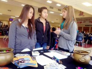Photo -  Moore High School senior Kendra Beedle, right, talks with two students about the dangers of texting and driving at a pledge drive recently at the school. Beedle wants students to sign pledges that they won't text while driving. PHOTO PROVIDED  <strong>PROVIDED</strong>